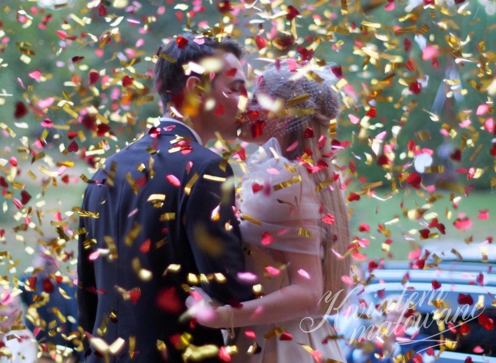 Nowożeńcy obsypani kolorowymi dekoracajami
