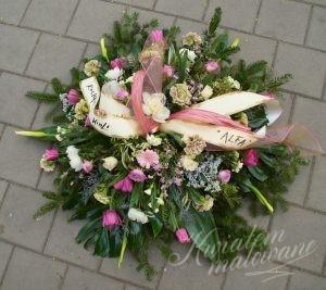 wieniec pogrzebowy wykonany z kilku rodzaju kwiatów i ze wstęgą