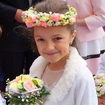 Wianek i bukiecik w rękach dziewczynki idącej do pierwszej komuni świętej