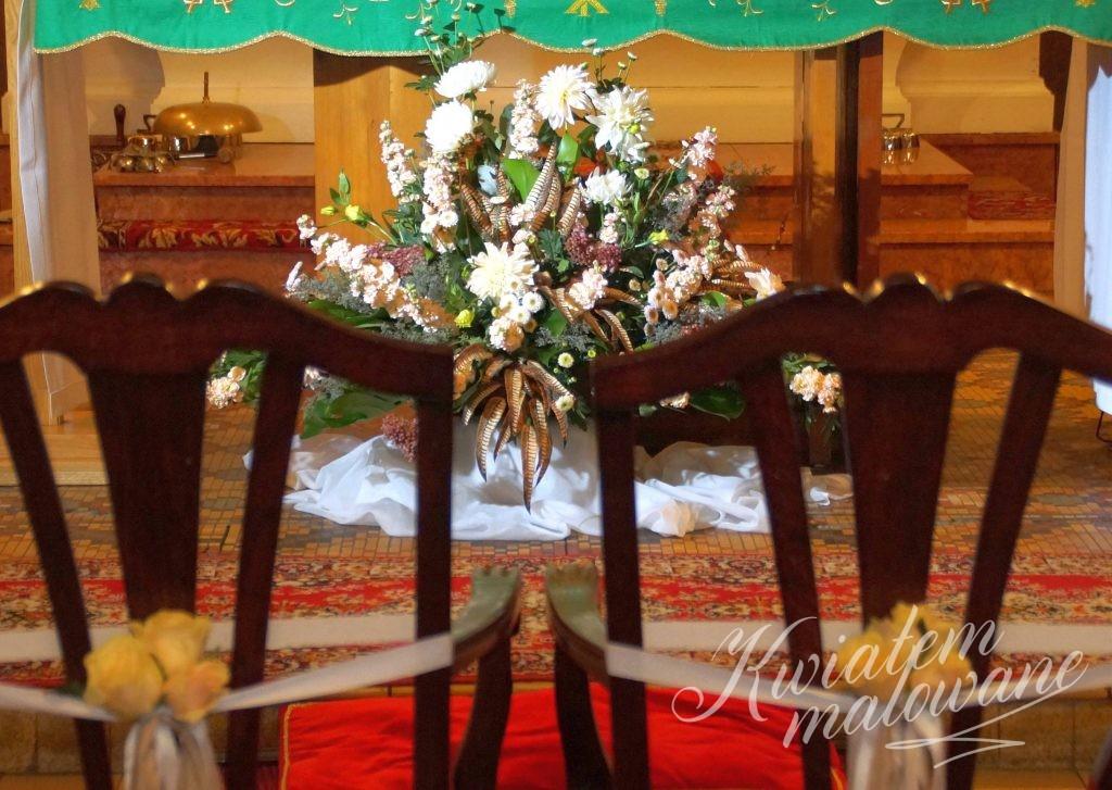 Przystrojone krzesła Młodej Pary w kościele
