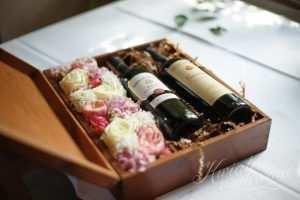 Butelki wina w pudełku i kwiatach